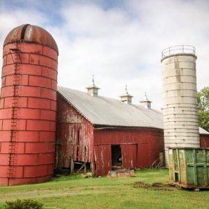 An old metal silo, accompanied by an old stave silo.