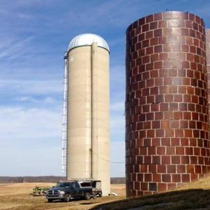 An older terra cotta silo, with a newer monolithic, concrete silo in the background.